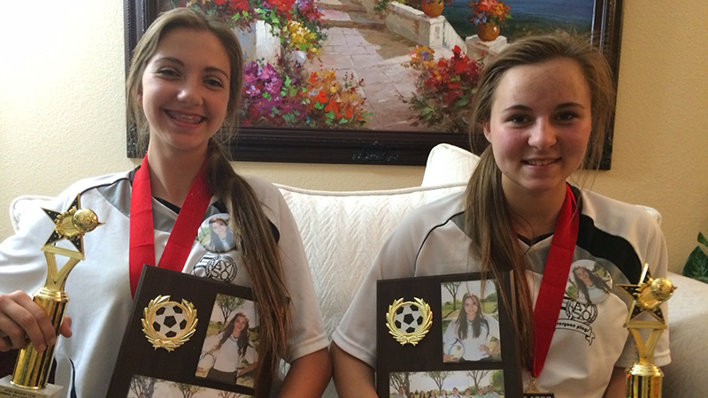 German international student and her host sister from Nevada with their soccer trophies and team pictures