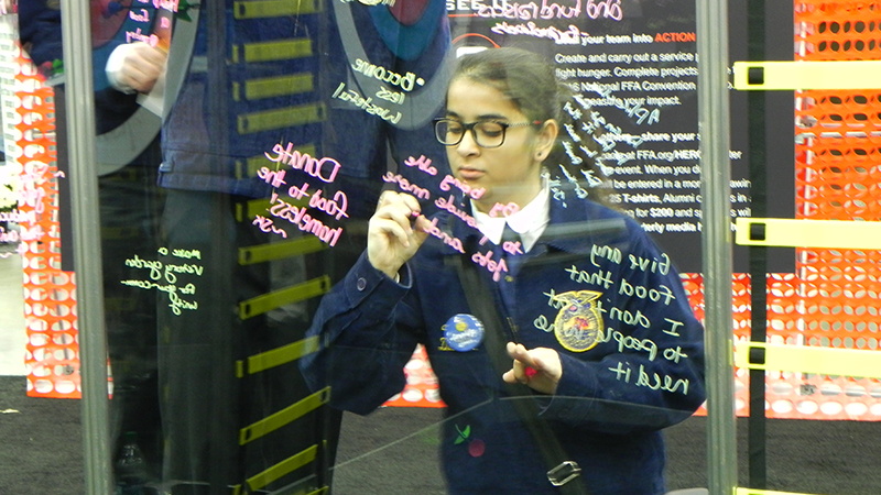 YES exchange student from Pakistan writes her thoughts on a wall at FFA national convention in Kentucky
