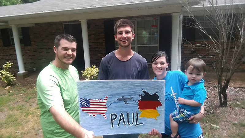 German high school exchange student in Minnesota with his host parents and little brother holding a welcome sign