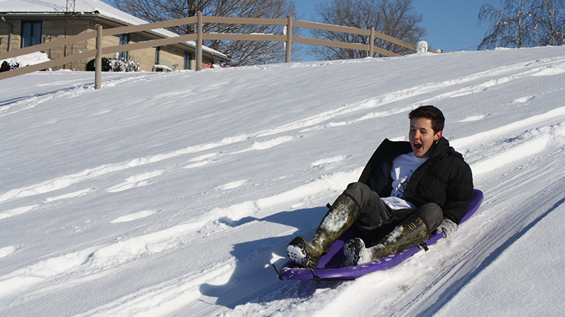 Brazilian PAX exchange student sledding down a hill in Indiana for the first time