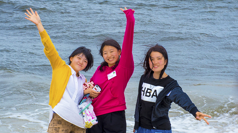 PAX foreign exchange students from Asia enjoying the Atlantic Ocean waves during an arrival orientation in New York