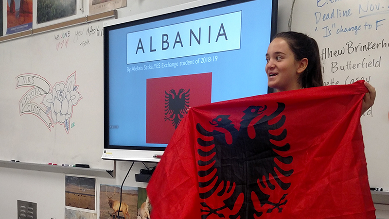 Albanian foreign exchange student presenting the Albanian flag and culture to her classmates in Utah during IEW