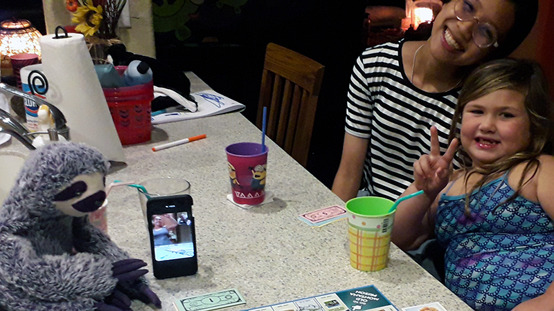 Thai exchange student playing virtual Monopoly with young host sister, host mom, and military host dad