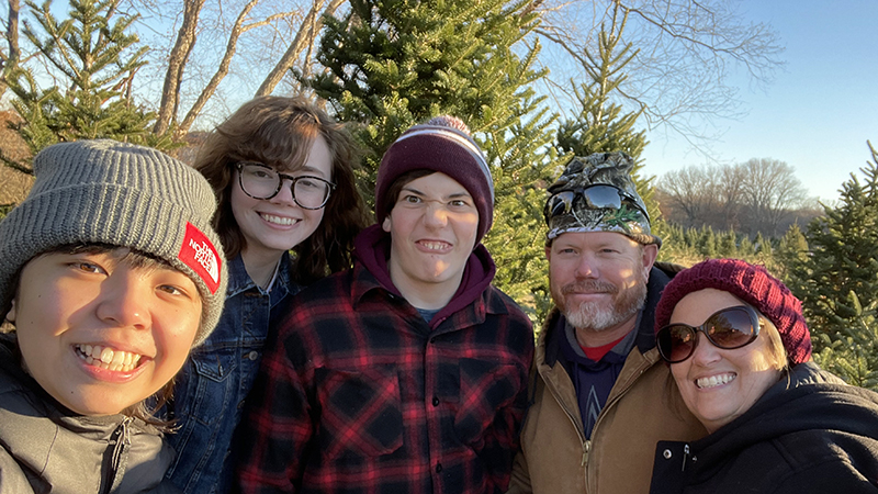 Japanese exchange student with her Iowa host family in a Christmas tree farm