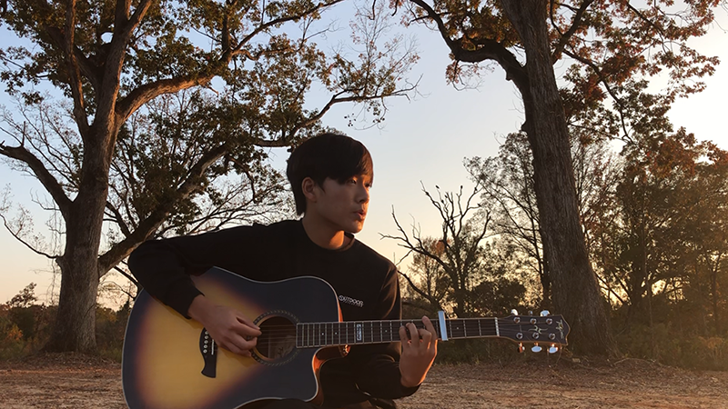Japanese exchange student playing acoustic guitar outdoors on an Arkansas evening