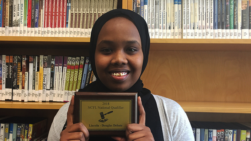 PAX exchange student from the Abaarso School in Somaliland presents her national debate qualifier plaque