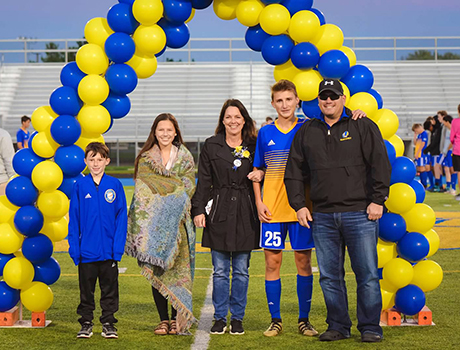 Polish PAX student wearing his soccer jersey poses with his host family on Senior Night