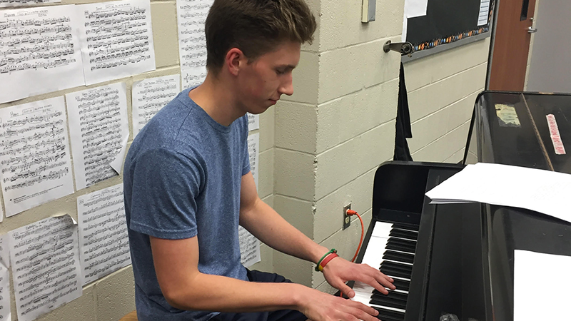 Future Leaders Exchange Program student from Lithuania playing the piano at practice at his Texas high school