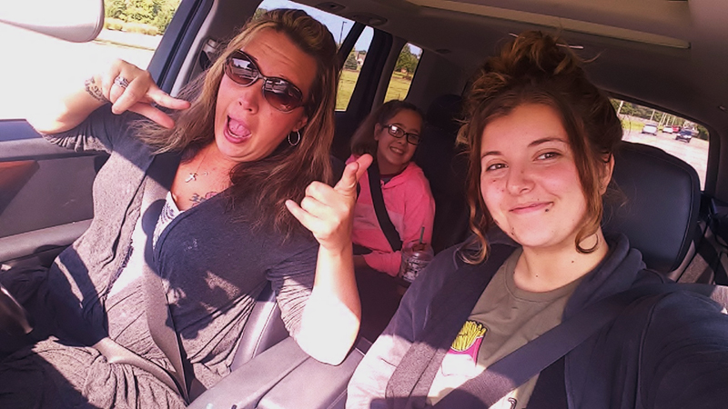 FLEX international student taking a selfie with her host mom and host sister in the car on their to a yard sale in Indiana