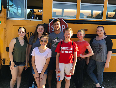International student from Lebanon with his American schoolmates in front of a yellow school bus in New Hampshire