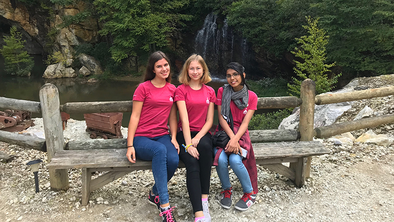 PAX international students from India, Ukraine, and Latvia in front of a waterfall on an enhancement trip in North Carolina