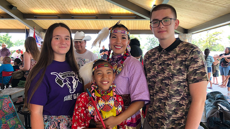 PAX students from Montenegro and Albania with Navajo dancers in traditional dress at a tribal dance competition in Utah