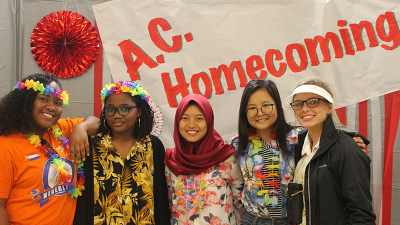 Exchange students from Mozambique, Suriname, Indonesia, and Thailand in front of a homecoming sign with their American friend