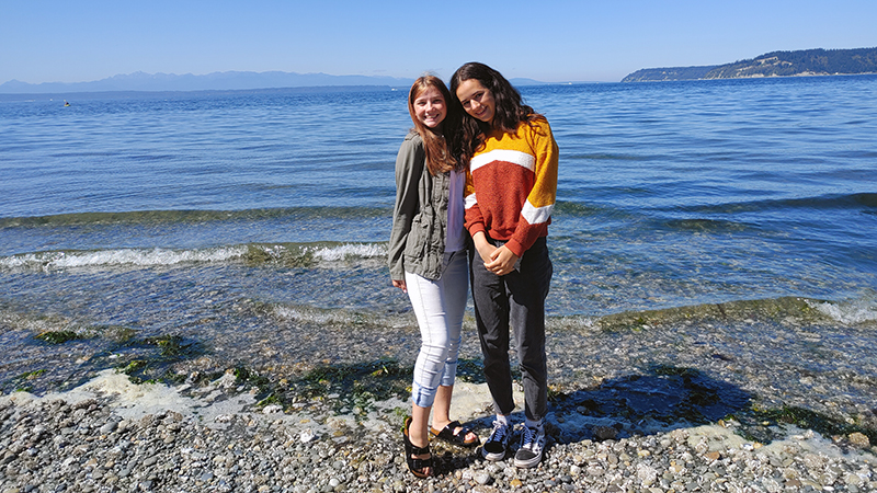 American host sister and female German exchange student pose in front of the Puget Sound