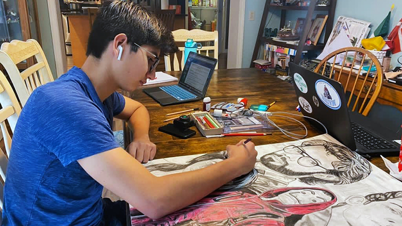 Mexican exchange student drawing at kitchen table
