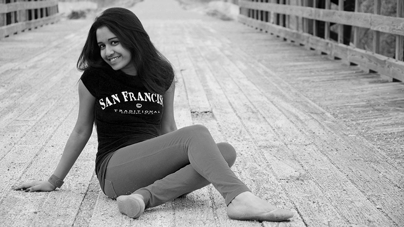 Young woman from Bangladesh poses on wooden bridge during exchange year in Michigan
