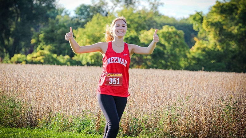 Latvian exchange student running in cross country meet gives the thumbs up