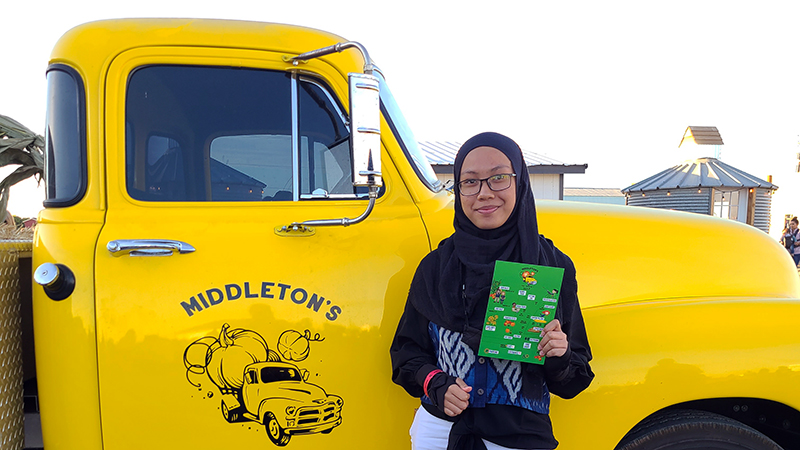 Indonesian exchange student poses in front of pickup truck at fall harvest festival