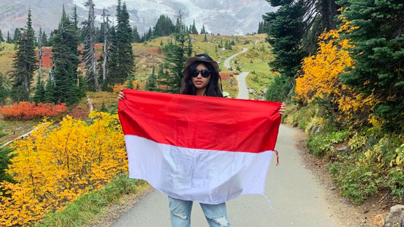 Indonesian exchange student holds country's flag in Pacific Northwest mountain scenery