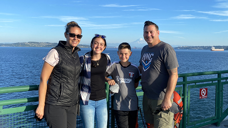 Spanish exchange students poses with American host family on a boat in the Pacific Northwest