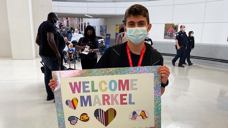 Spanish exchange student holds welcome sign at airport