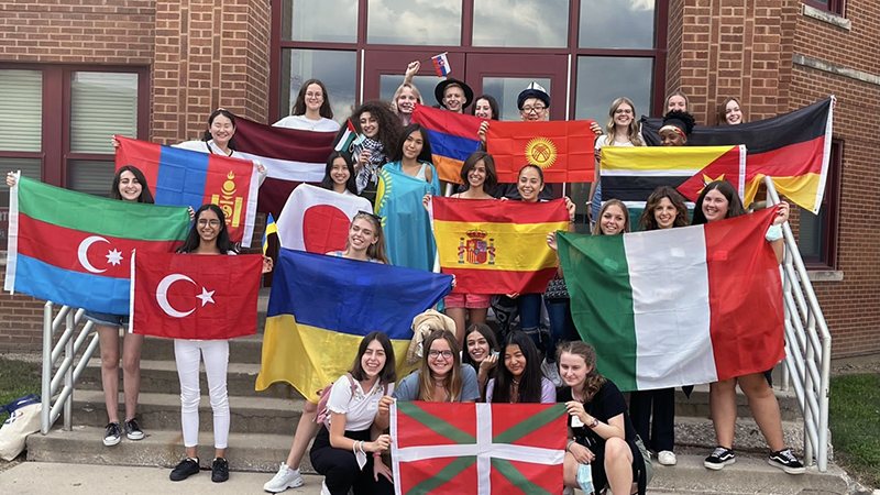 Exchange students from many countries hold their flags on the steps of an American high school