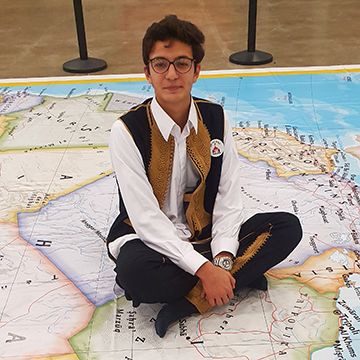 High school boy from Libya in traditional Libyan clothing sitting on map of the world