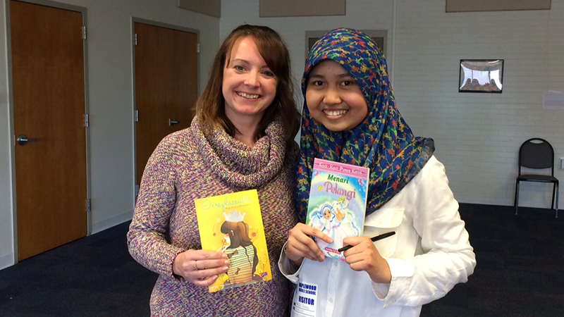 YES student Ayunda from Indonesia and her teacher in Wisconsin hold books written by Ayunda herself