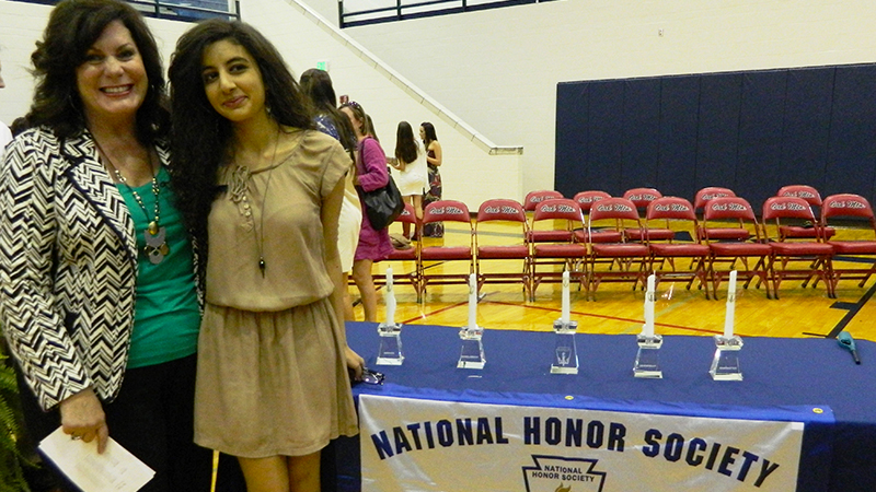 Foreign exchange student from Jordan stands behind a podium after being inducted into the National Honor Society