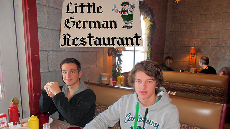 PAX exchange student from Germany shows Australian host brother traditional food at a German restaurant in Maine