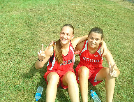 FLEX international student from Ukraine and her American friend sit on the ground in their cross country uniforms
