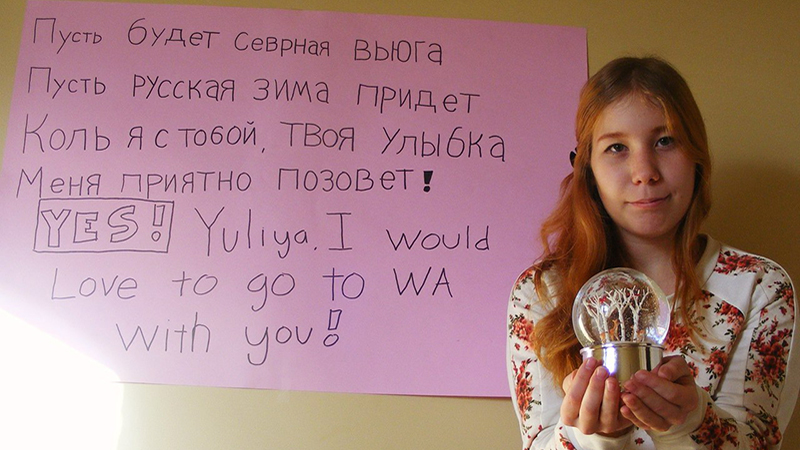 FLEX student from Russia stands in front of a poster displaying a poem written in Russian by her American friend